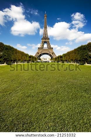 Beautiful photo of the Eiffel tower in Paris with gorgeous colors and wide angle central perspective. Lots of copy space grass.