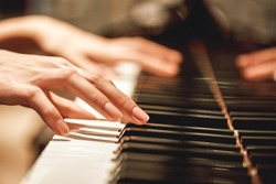 Beautiful Piano Melody...Close up view of female hands playing on piano her favorite classical music. Musical instrument. Music education. Piano keyboard