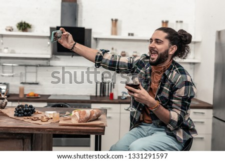 Beautiful pic. Delighted happy man holding a glass of wine while taking selfie