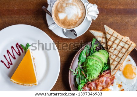 beautiful picture from above for a hearty breakfast with scrambled eggs with bacon and avocado, a portion of cheesecake with freshly brewed coffee