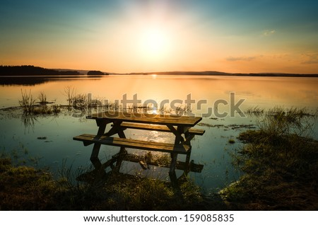 beautiful picture of a table with bench by a lake with the sun and sunbeams in the sky