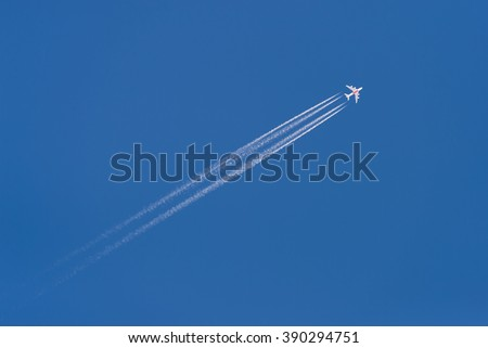 Beautiful picture of white plane flying with trail in blue sky #390294751