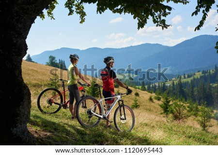 Beautiful picture of young bikers couple, man and woman standing with bikes on grassy hill enjoying fantastic view of magnificent blue mountain range background in oval frame of big green tree branch.