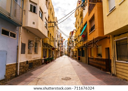 beautiful, picturesque street, narrow road, colorful facades of buildings, Spanish architecture, sunny day #711676324