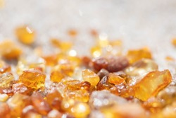 Beautiful pieces of amber on the sandy beach, amber background, close up