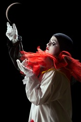 Beautiful Pierrot clown playing mime with the moon