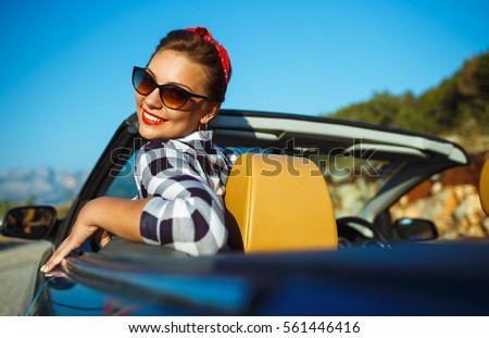 Beautiful pin up woman sitting in cabriolet, enjoying trip on luxury modern car with open roof, fashionable lifestyle concept stock photo