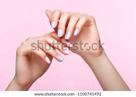 Beautiful pink and blue manicure with crystals on female hand. Close-up. Picture taken in the studio
