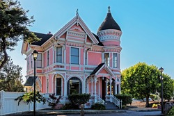Beautiful pink and white traditional Victorian house. A garden of flowers, lawn and trees. In the background is a beautiful, cloudless, baby blue sky.