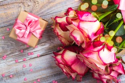 Beautiful pink and yellow roses and gift box with pink bow on wooden background. St Valentines day or mothers day concept. Copy space