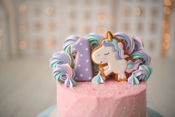 Beautiful pink cake for children's birthday with a unicorn. Gingerbread in the form of numbers one. On the cake are delicious multi-colored marshmallows.