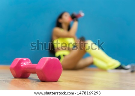 Beautiful pink dumb-bell shaped figure lying on the floor at blur background of sporty girl sitting with a drink. Concept of exercising in gym and doing fitness. Active lifestyle of sportswoman.