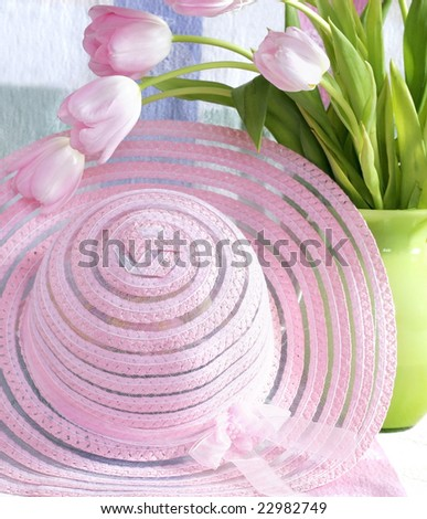 beautiful pink hat with pink tulips in green vase