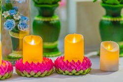 Beautiful pink kratong lotus with yellow candle and fire flame. Conccept for loy kratongs festival celebrated in Thailand.