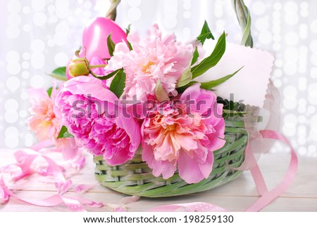 beautiful pink peony in wicker basket with blank card (shallow focus)