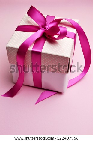 Beautiful pink present gift in white box and polka dot lid, with candy hot fuchsia pink ribbon bow set against a pretty pink background, for Valentine, Christmas, Birthday or Mothers Day gift.