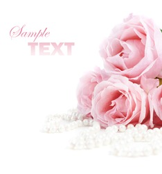 Beautiful pink roses and white pearls isolated over white background. Closeup flower bouquet and jewels with copyspace.