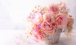 Beautiful pink roses in basket on vintage wooden table. Shabby chic style. Flower composition for holiday with copy space.