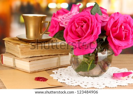 Beautiful pink roses in vase on wooden table on room background