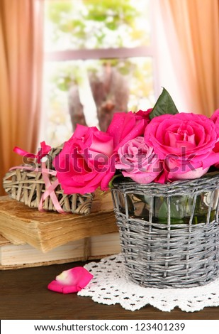 Beautiful pink roses in vase on wooden table on window background