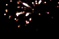 Beautiful pink single exploding firework bokeh against black sky background on new years eve