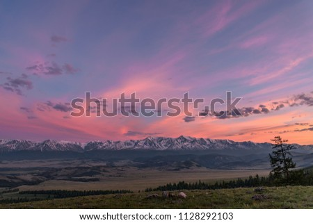 Beautiful pink sunset over the mountains covered with snow, valley and forest on the slopes of the mountains