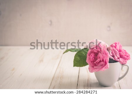 Beautiful pink tea roses on a white wooden background. Romantic background. Vintage shabby frame