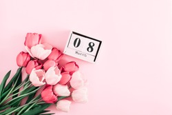 Beautiful pink tulips and calendar on pastel pink background. Concept Women's Day, March 8. 8th march. Flat lay, top view, copy space