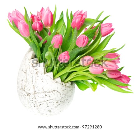 beautiful pink tulips in the easter egg vase. spring flowers with water drops