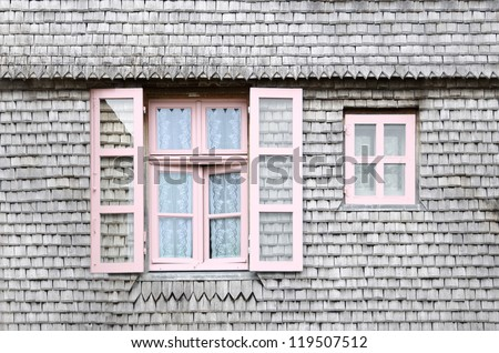 Beautiful pink windows on facade of a wooden house. Wood windows, detail of an old wooden facade.