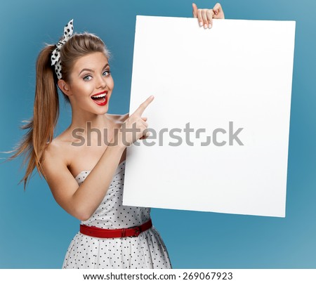Beautiful pinup girl shows forefinger on the blank banner / photo set of young American pin-up model on blue background with space for text