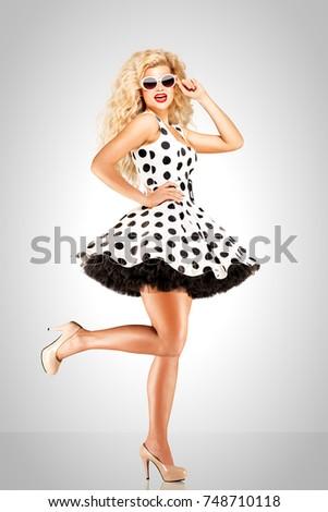 Beautiful pinup model wearing polka dot dress and sunglasses on grey background. #748710118