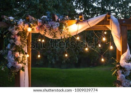 Beautiful place made with wooden square and floral decorations for outside wedding ceremony in wood. #1009039774