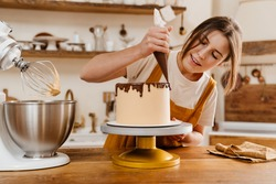 Beautiful pleased pastry chef woman making cake with chocolate cream at cozy kitchen