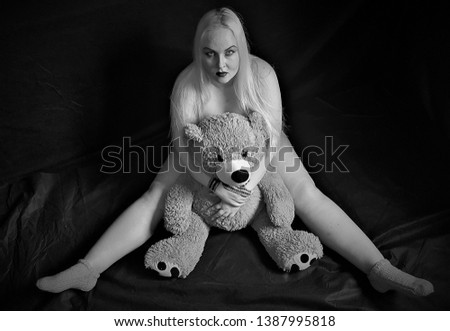 Beautiful plump blonde poses for the camera along with plush toys.