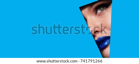 Beautiful plump bright lips of blue metallic look into the hole of colored paper. #741791266