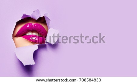 Beautiful plump bright lips of pink color peep into the slit of colored paper.Cosmetics, make-up, beauty salon, make-up artist, lilac lip gloss, beautiful teeth, sales.