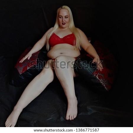 Beautiful plump woman posing in red underwear. She is very full.