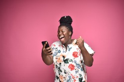 beautiful plus size black woman feeling excited and happy while holding and looking at her phone