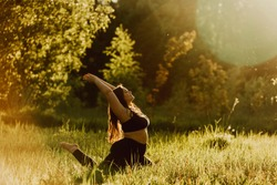Beautiful plus size girl doing yoga in nature on a sunny summer day. Body positive, sports for women.