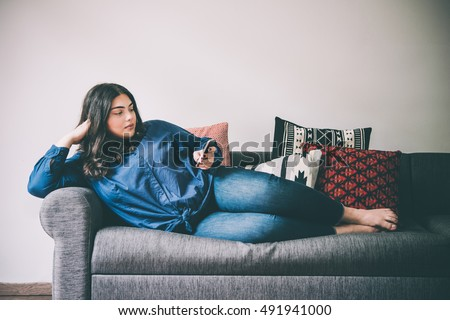 Beautiful plus size girl lying on the sofa with moblile phone. Toned picture #491941000