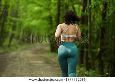 Beautiful plus size runner woman running on a dirt road in the forest Сток-фото ©