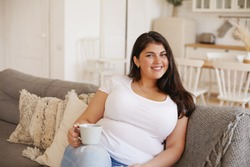 Beautiful plus size woman in casual clothes sitting on couch in living room with cup of morning coffee, smiling, thinking about new day, making plans. People, lifestyle and domesticity concept
