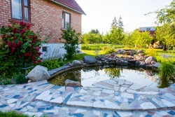 Beautiful pond in a backyard of a red brick home surrounded with stone during summer