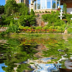 Beautiful pond in front of garden with sculptures, fountains and flowers - sunset light. Shot in Ukraine.