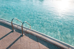 Beautiful pool with a Metal Handrails Descent and blue water at sunset. Swimming and summer rest concept