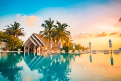 Beautiful poolside and sunset sky. Luxurious tropical beach landscape, deck chairs and loungers and water reflection.