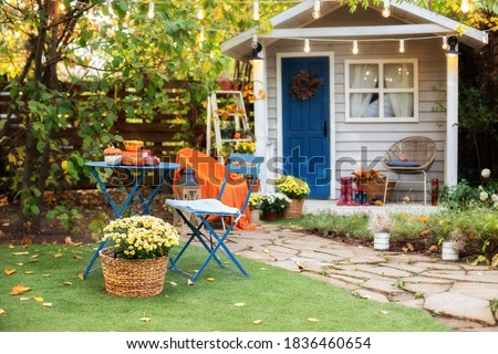 Beautiful porch home with autumn decorations on thanksgiving.   Garden table and chairs with apples and pumpkins on autumn yard. Terrace with retro light bulbs garlands. halloween. Interior cozy patio