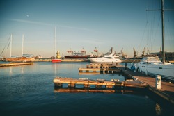Beautiful port of Odessa, Black sea. Luxury yachts, ships and fishing boats standing in rows in harbor. Rich people traveling around the world. Sunny evening