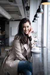 Beautiful portrait Asian girl sitting on counter bar in coffee shop putting hand on her chin looking at camera with smile. The cup of coffee put on the bar next to window.